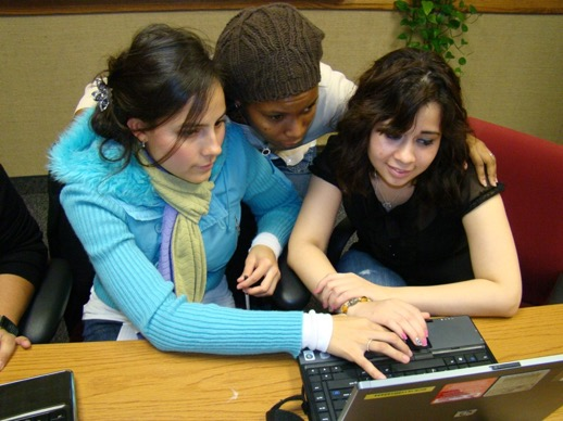 three women working together on a laptop